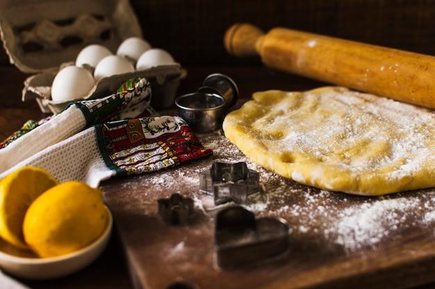 Pâte et rouleau à pâtisserie près des emporte-pièces et des serviettes