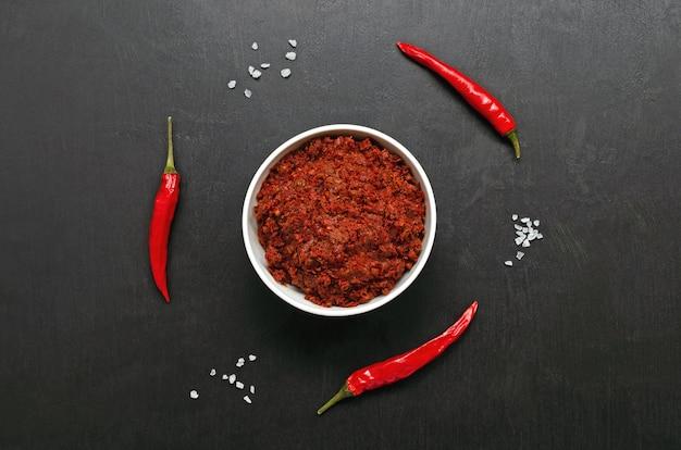 Pâte de sauce au piment chaud maghrébin traditionnel harissa sur fond sombre, cuisine tunisienne et arabe, orientation horizontale, espace copie