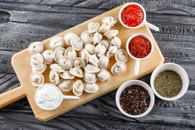 De la pâte avec de la sauce, des épices dans des bols sur une planche à découper sur une surface en bois gris, vue de dessus.