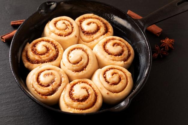 Pâte soufflée de concept de nourriture de petits pains à la cannelle faits maison levés dans un poêle en fonte