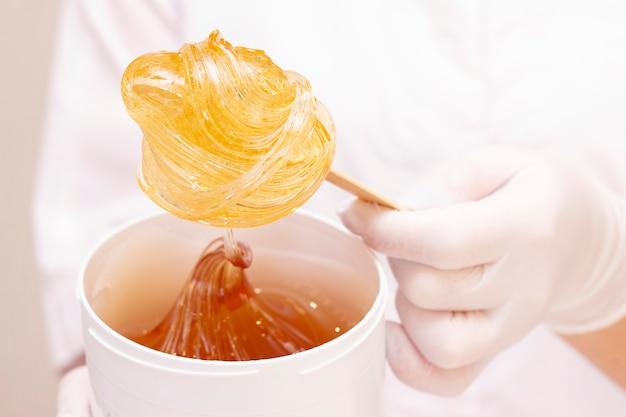 Pâte à sucre liquide ou cire à épiler sur un bâton de bois en gros plan sur un blanc, contre l'uniforme d'un maître d'épilation.
