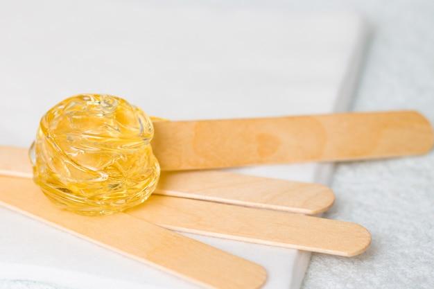 Pâte de sucre ou miel de cire à épiler à l'aide de bâtonnets de spatule à cirer en bois
