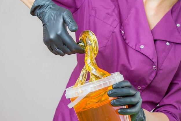 Pâte de sucre ou miel de cire à épiler avec des gants noirs, mains du cosmétologue au salon spa