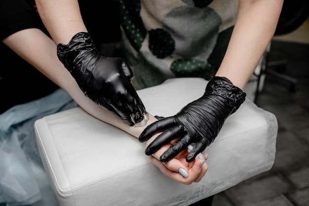 Pâte de sucre ou miel de cire à épiler avec des gants noirs