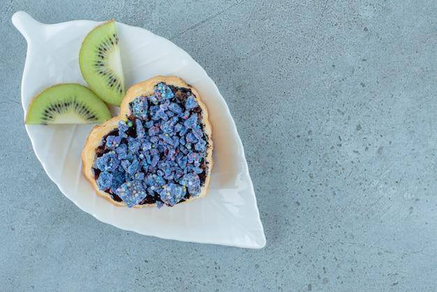 Pâte sucrée en forme de coeur avec des tranches de kiwi.