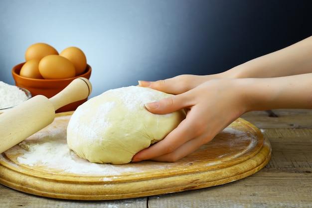 Pâte sur la table de la cuisine avec des accessoires de cuisine