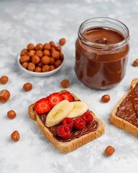 Pâte à tartiner au chocolat ou crème de nougat aux noisettes dans un bocal en verre sur du béton, fond
