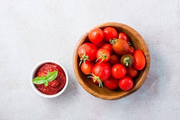 Pâte de tomate et feuilles de basilic dans un bol et tomates sur une assiette sur fond clair. nourriture végétale et végétarienne. vitamines et régime détox. vue de dessus