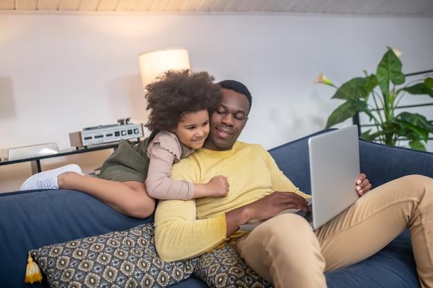 Paternité. jeune homme souriant à la peau foncée avec un ordinateur portable et étreignant une petite fille intéressée regardant l'écran exigeant de l'attention