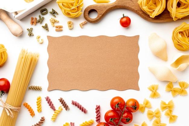 Pâtes alimentaires non cuites mélanger tomates et fromage à pâte dure avec maquette en carton