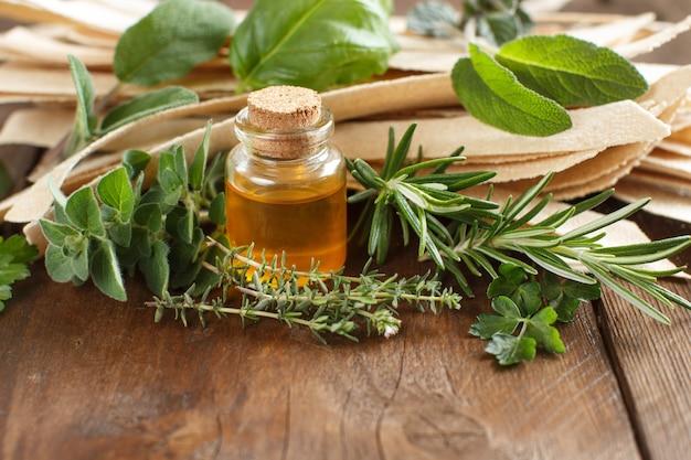 Pâtes artisanales à grains entiers, huile d'olive et herbes sur la vieille table en bois