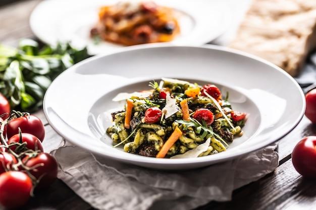 Pâtes au pesto vert, tomates cerises, parmesan et huile d'olive dans une assiette.