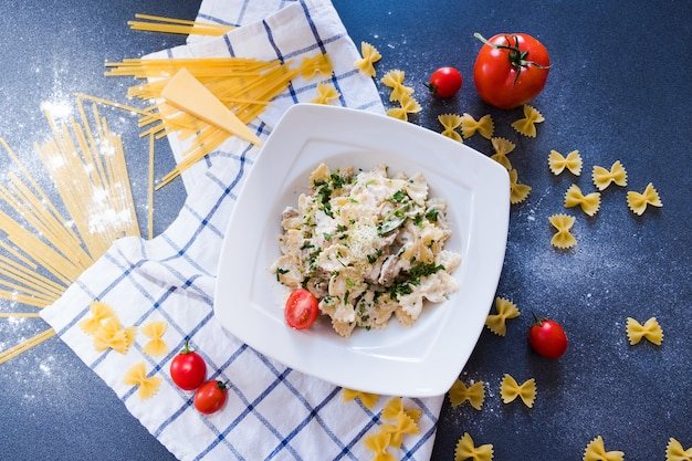 Pâtes au poulet, champignons, crème, poivron vert, oignon, persil, basilic sur plaque blanche