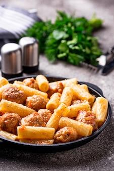 Pâtes aux boulettes de viande à la sauce tomate.