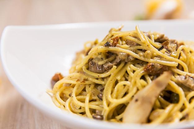 Pâtes aux champignons dans une assiette blanche sur une table en bois clair dans un restaurant