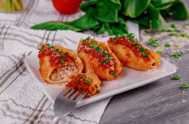 Pâtes aux coquilles géantes fourrées à la ricotta et au basilic.