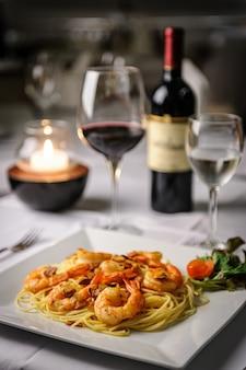 Pâtes aux crevettes à l'ail et à l'huile d'olive sur une plaque blanche à table