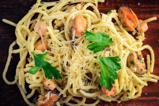 Pâtes aux fruits de mer, crevettes et moules, parsemées de feuilles de persil et de fromage.