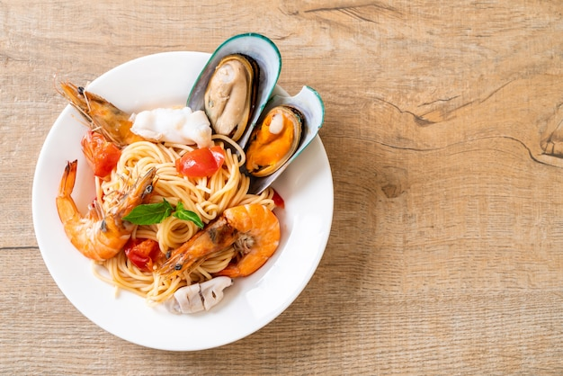 Pâtes aux fruits de mer spaghetti aux palourdes, crevettes, squis, moules et tomates