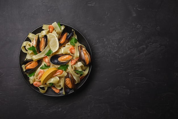 Pâtes aux fruits de mer sur la table en pierre. moules et crevettes. vue de dessus avec espace de copie.