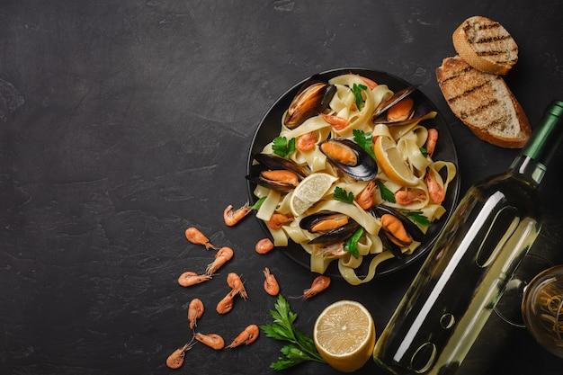 Pâtes aux fruits de mer et vin blanc sur une table en pierre. moules et crevettes. vue de dessus.