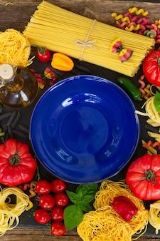 Pâtes aux ingrédients et assiette bleue vide