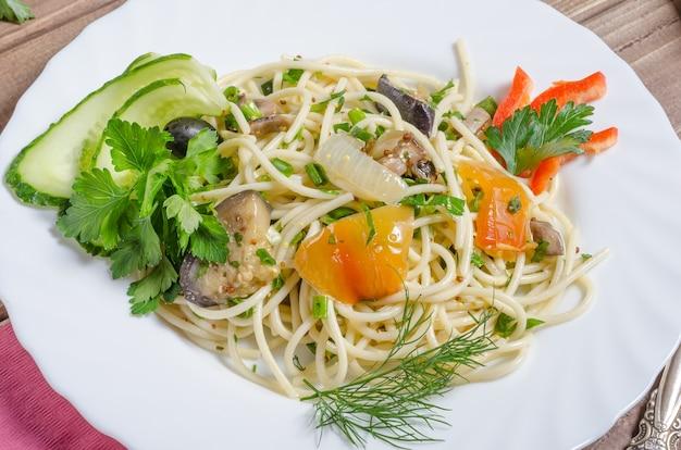 Pâtes aux légumes avec compote d'aubergines et de poivre sur un gros plan de plaque blanche