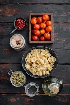 Pâtes aux légumes et ingrédients du thon sur la vieille table en bois, mise à plat