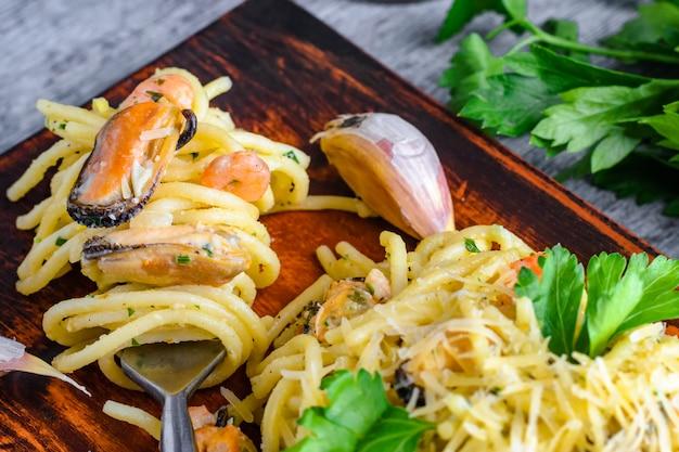 Pâtes aux moules de fruits de mer et aux crevettes dans une sauce crémeuse sur une assiette.