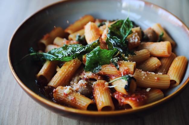 Pâtes aux saucisses à la sauce tomate sur fond de bois, cuisine italienne