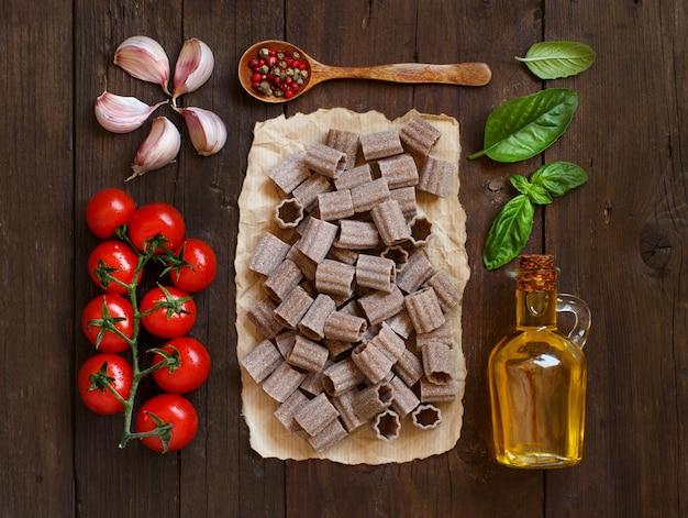 Pâtes de blé entier, légumes, herbes et huile d'olive sur fond de bois