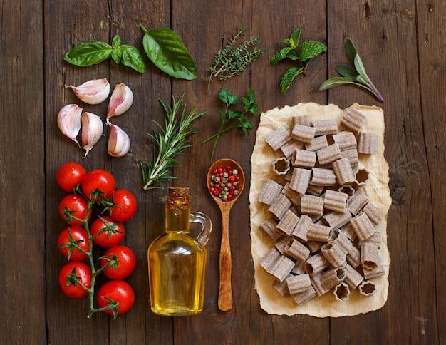 Pâtes de blé entier, légumes, herbes et huile d'olive sur table en bois
