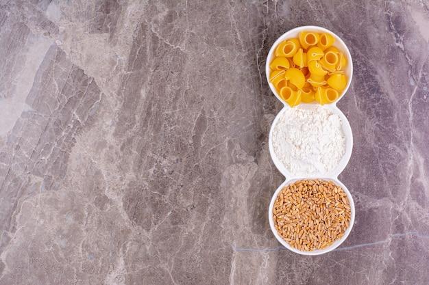 Pâtes, blé et farine mélangée dans trois tasses blanches