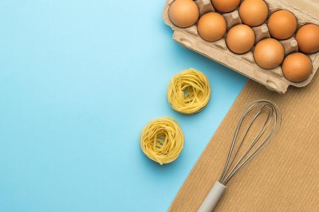 Pâtes, une boîte d'œufs et un fouet pour fouetter sur fond bleu. ingrédients pour faire des pâtes.