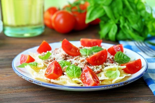 Pâtes à la bolognaise aux tomates cerises en plaque blanche sur table en bois, gros plan
