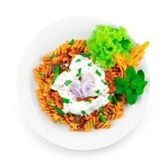 Pâtes à la bolognaise sauce curry aux lentilles sur la sauce au yaourt et à la menthe traditionnelle afghanistan, inde food fusion style décoration sculpture chili et légumes topview