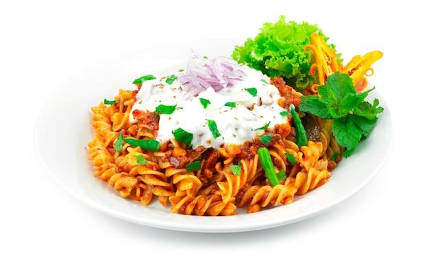 Pâtes à la bolognaise sauce curry aux lentilles sur la sauce au yogourt et à la menthe traditionnelle afghanistan, inde food fusion style décoration sculpture chili et légumes sideview