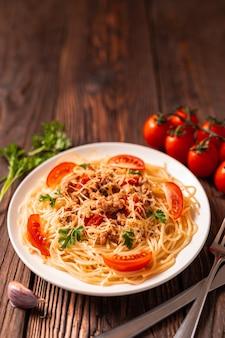 Pâtes à la bolognaise avec sauce tomate et viande hachée, parmesan râpé et persil frais - pâtes italiennes saines et faites maison