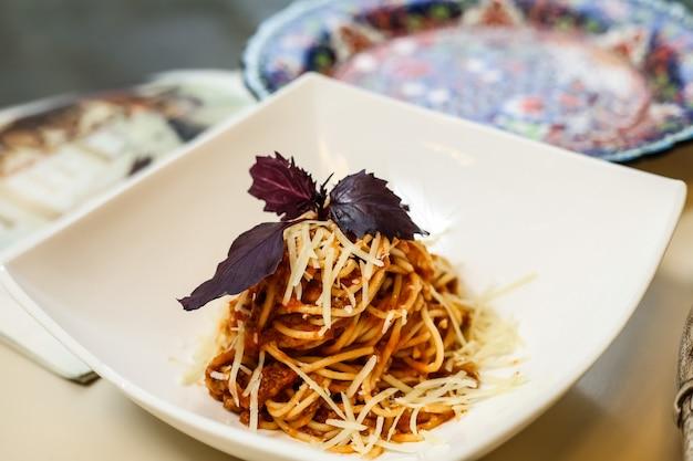 Pâtes bolognaise viande basilic parmesan vue de côté