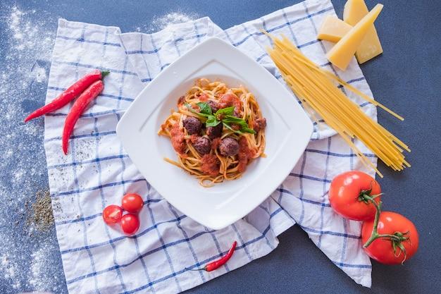 Pâtes bolognaises sur assiette blanche. spaghetti sur fond bleu