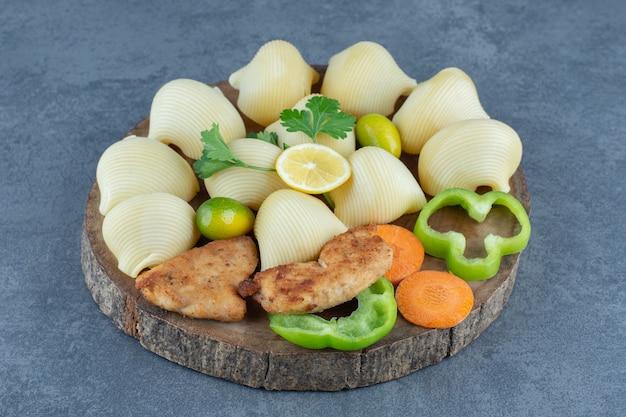 Pâtes bouillies et ailes de poulet sur morceau de bois.