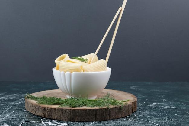 Pâtes bouillies dans un bol blanc avec des baguettes et de la coriandre. photo de haute qualité