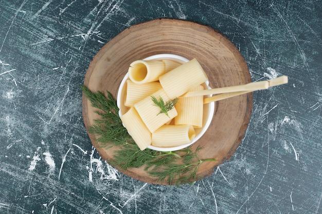 Pâtes bouillies dans un bol blanc avec des baguettes et de la coriandre.