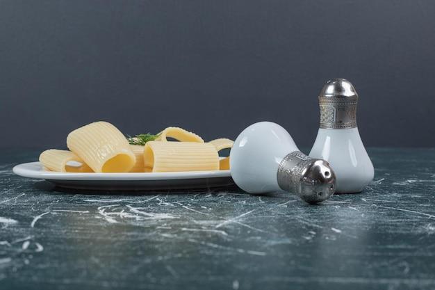Pâtes bouillies sur plaque blanche avec du sel.