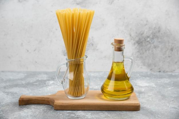 Pâtes et une bouteille d'huile d'olive extra vierge sur une planche en bois.