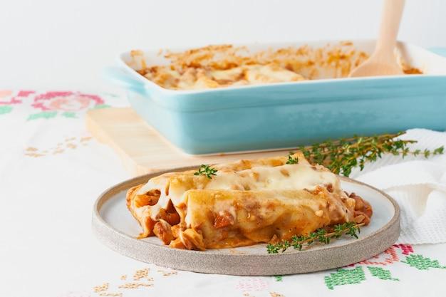 Pâtes cannelloni avec garniture de boeuf haché, tomates, cuites au four avec sauce béchamel aux tomates
