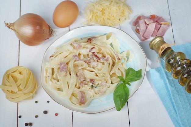 Pâtes carbonara aux tagliatelles italiennes et tous les ingrédients étalés sur le bord de l'assiette.