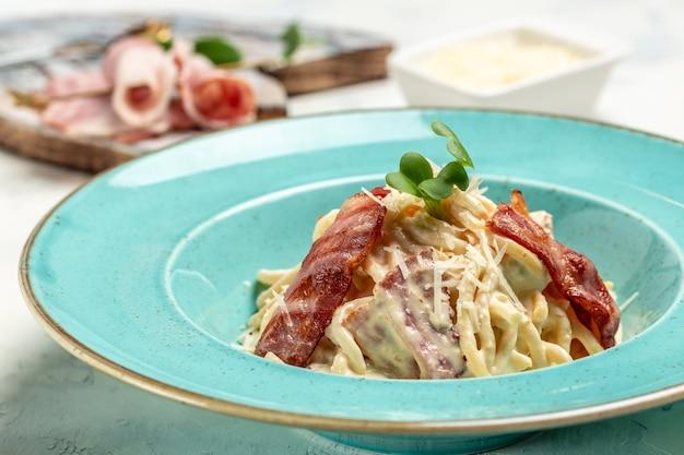 Pâtes carbonara bacon, fromage et sauce à la crème servis au restaurant. nourriture de restaurant. bannière, menu, lieu de recette pour le texte, vue de dessus.