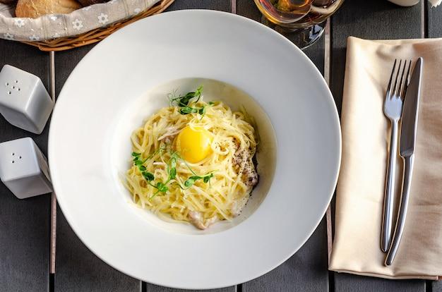 Pâtes carbonara sur plaque blanche au parmesan et jaune sur fond blanc