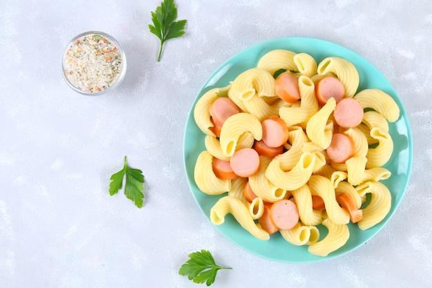 Pâtes cavatappi ou cellentani avec des saucisses sur une table grise